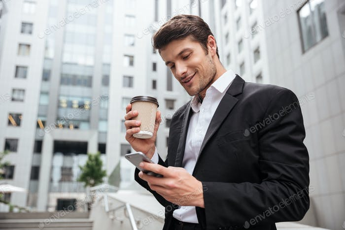 Smiling young businessman drinking coffee and using cell phone outdoors