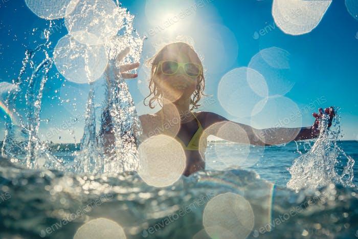 Glückliches Kind spielen im Meer