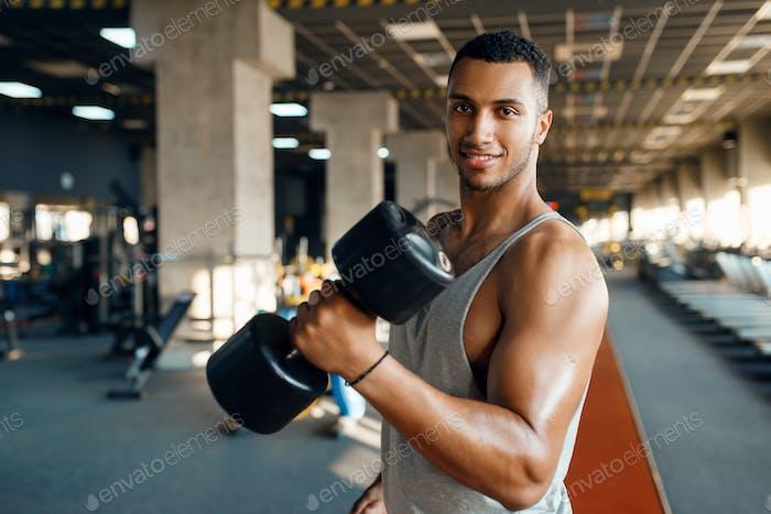 Мускулистый человек позирует с тяжелой гантели в тренажерном зале
