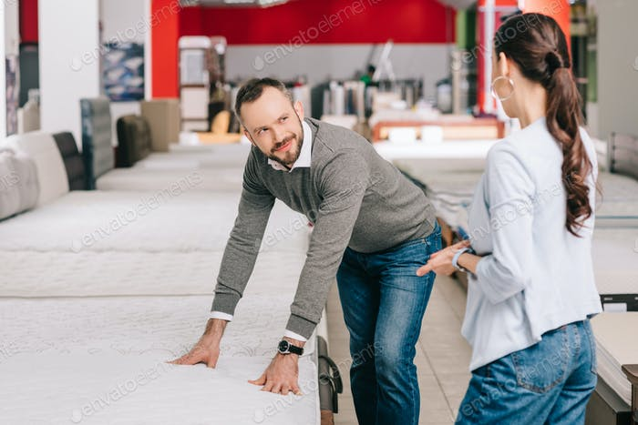 couple choosing mattress together in furniture shop