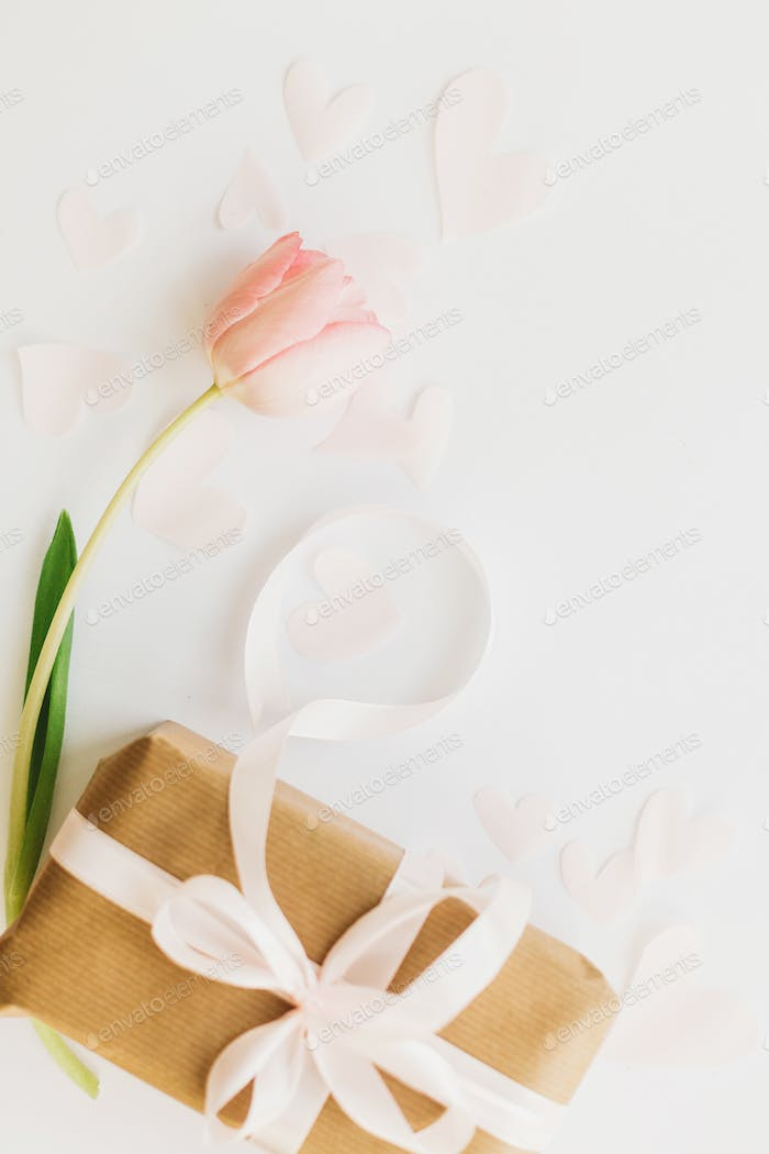 Pink tulip flat lay and gift box with ribbon on white background, space for text