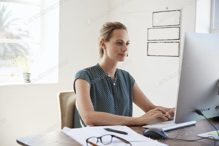 Young white woman working in office using computer, close up