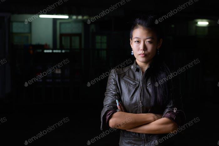 Schöne asiatische rebellische Frau mit Armen gekreuzt im Freien in der Nacht