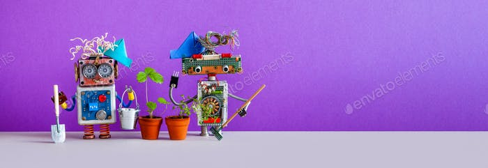 Two gardener steampunk toys with a strawberry bush grown in a flower pot.