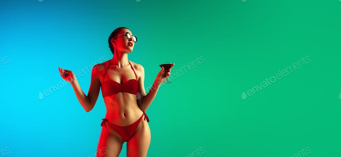 Fashion portrait of seductive girl in stylish swimwear posing on a bright gradient background