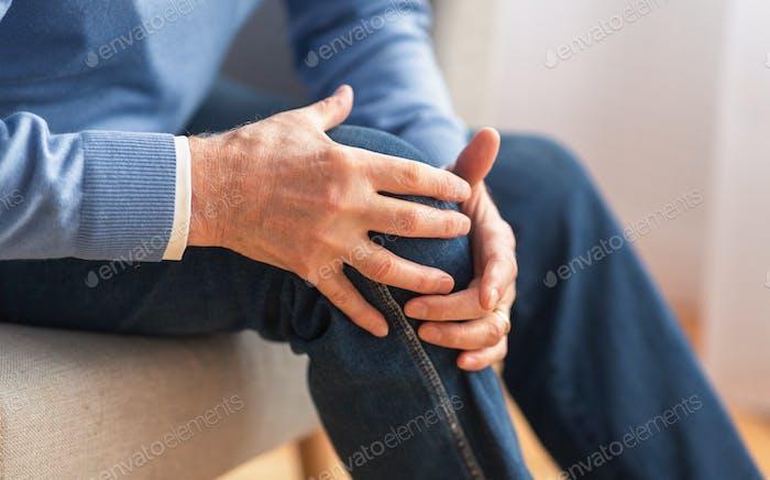 Senior man massaging his knee sitting on sofa indoor, cropped