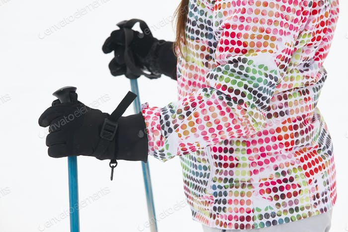 Woman ready to ski with sticks and gloves. Winter sports