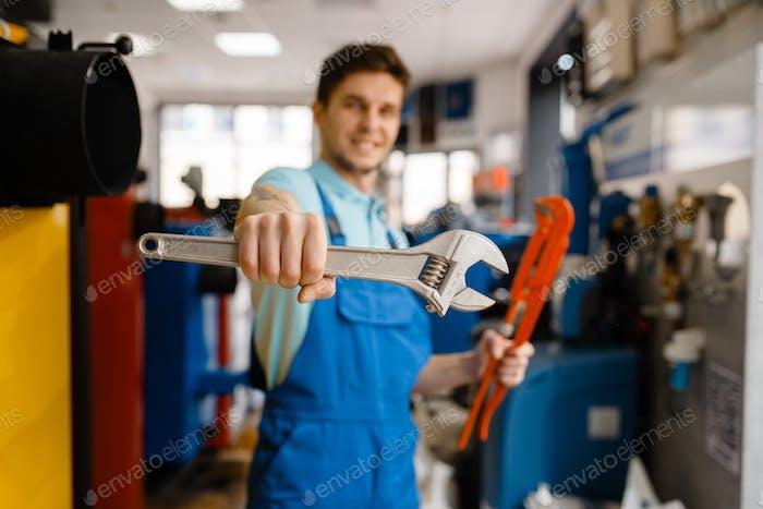 Plomero muestra llaves de tubería en una tienda de fontanería