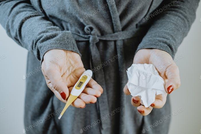 Weibliche Hände mit einem Thermometer und einem Taschentuch. Kaltes Konzept