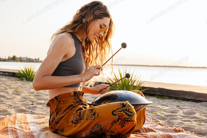Woman playing music on drum at the beach