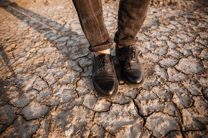 Men legs standing at the dessert dry ground