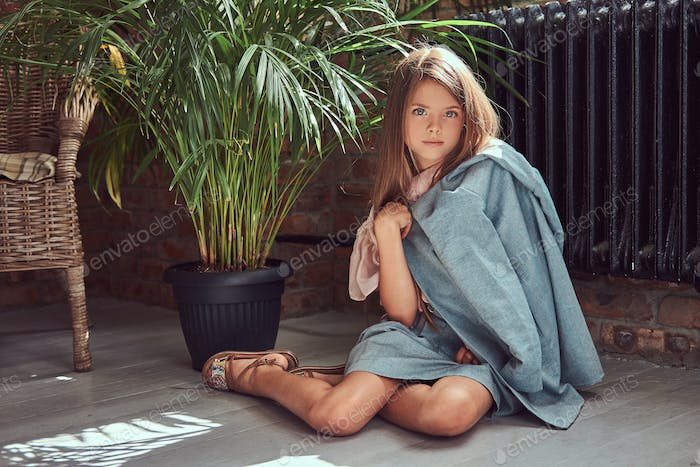 Cute little girl with long brown hair and piercing glance wearing a stylish dress at home