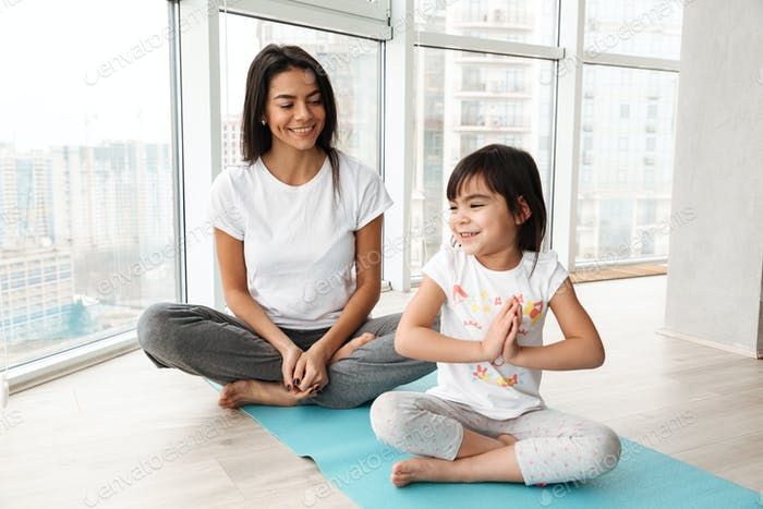 Happy people woman and little kid practicing yoga indoor, sittin