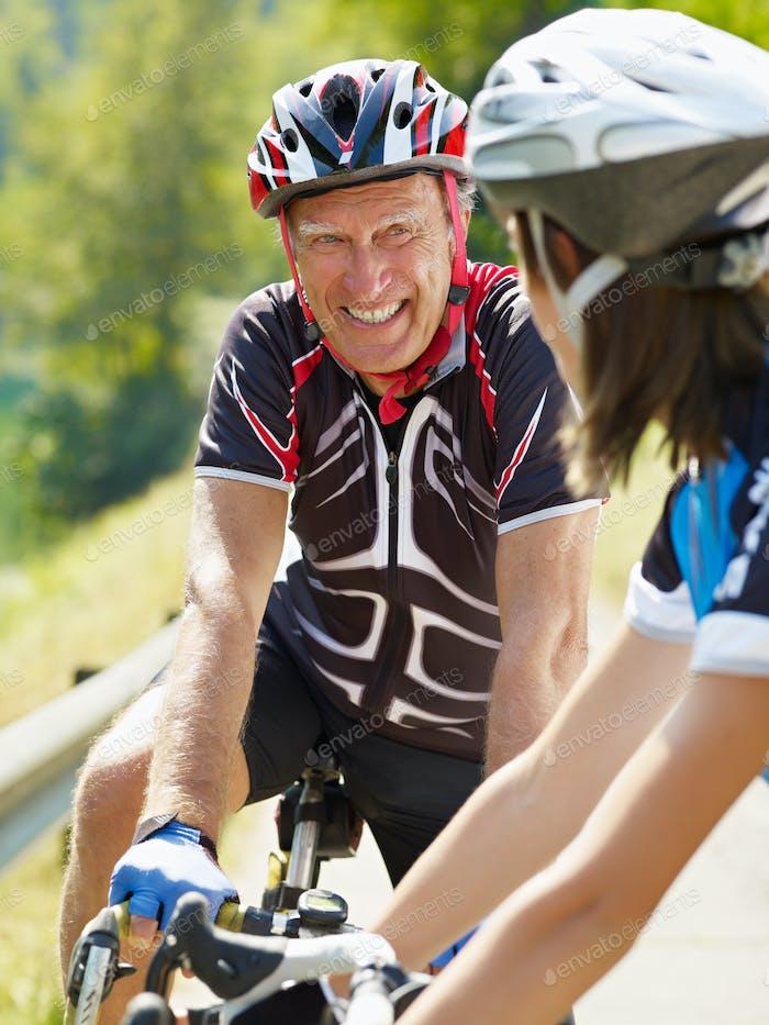 senior mann training auf fahrrad mit enkelin