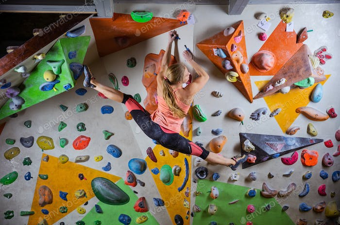 Young woman doing splits to reach next handhold while bouldering
