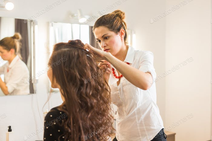 working day inside the beauty salon. Hairdresser makes hair styling.