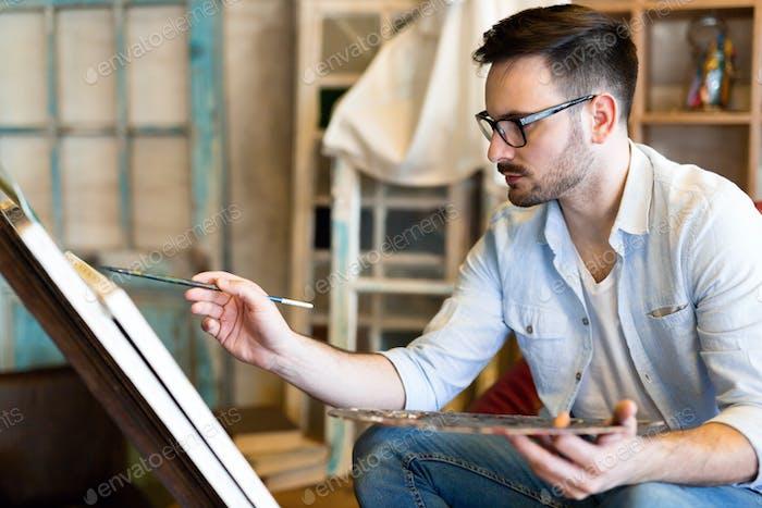 porträt von männlichen künstler arbeiten auf malerei in studio