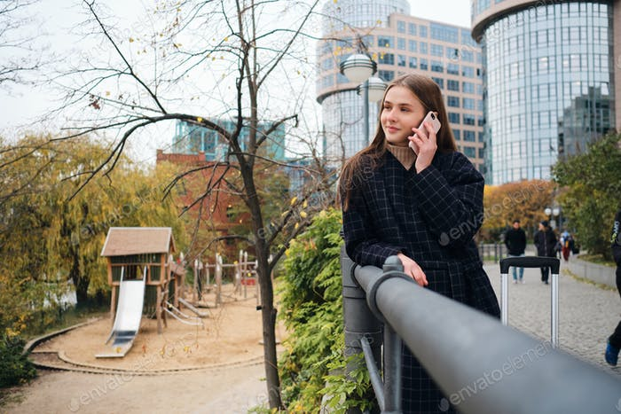 Pretty smiling girl in coat happily talking on cellphone in park