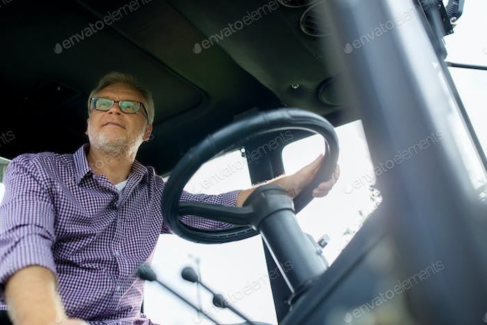 senior man driving tractor at farm