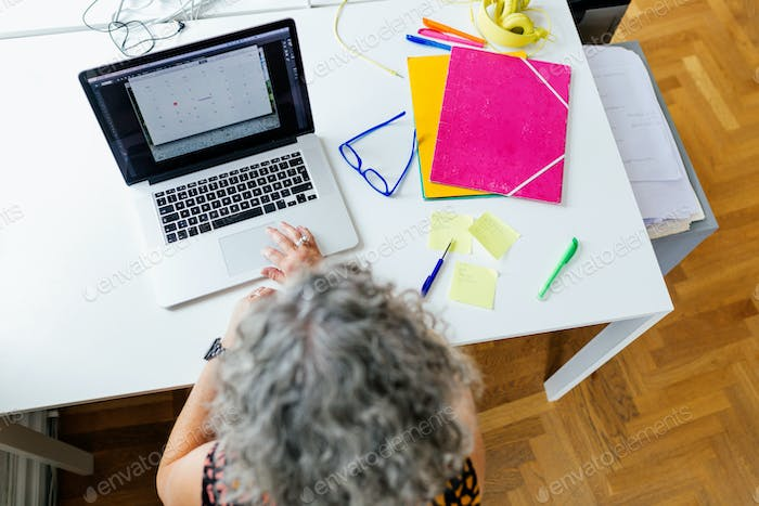 Elevated view of businesswoman using laptop in office