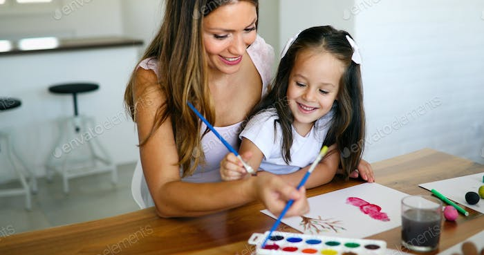 Mother looking how her child daughter drawing