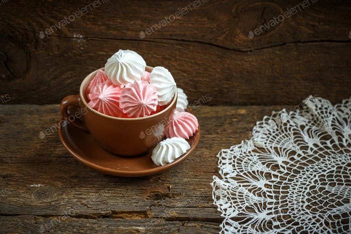 Pink and white meringues in a cup on old wooden background