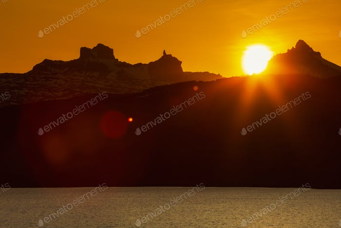 Beautiful Sunset in Rocky Mountains and Lake Shore, Red Orange Sun Sets Behind Silhouette of Cliff