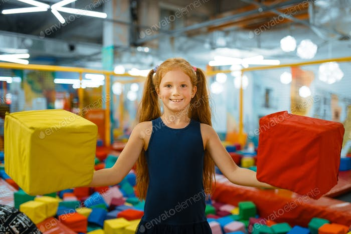 Adorable little girl playing with soft cubes