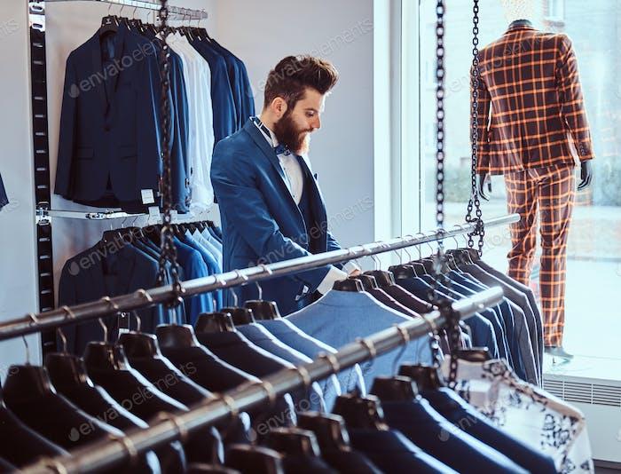Бородатая мастерская, одетая в синий элегантный костюм, работает в магазине мужской одежды.
