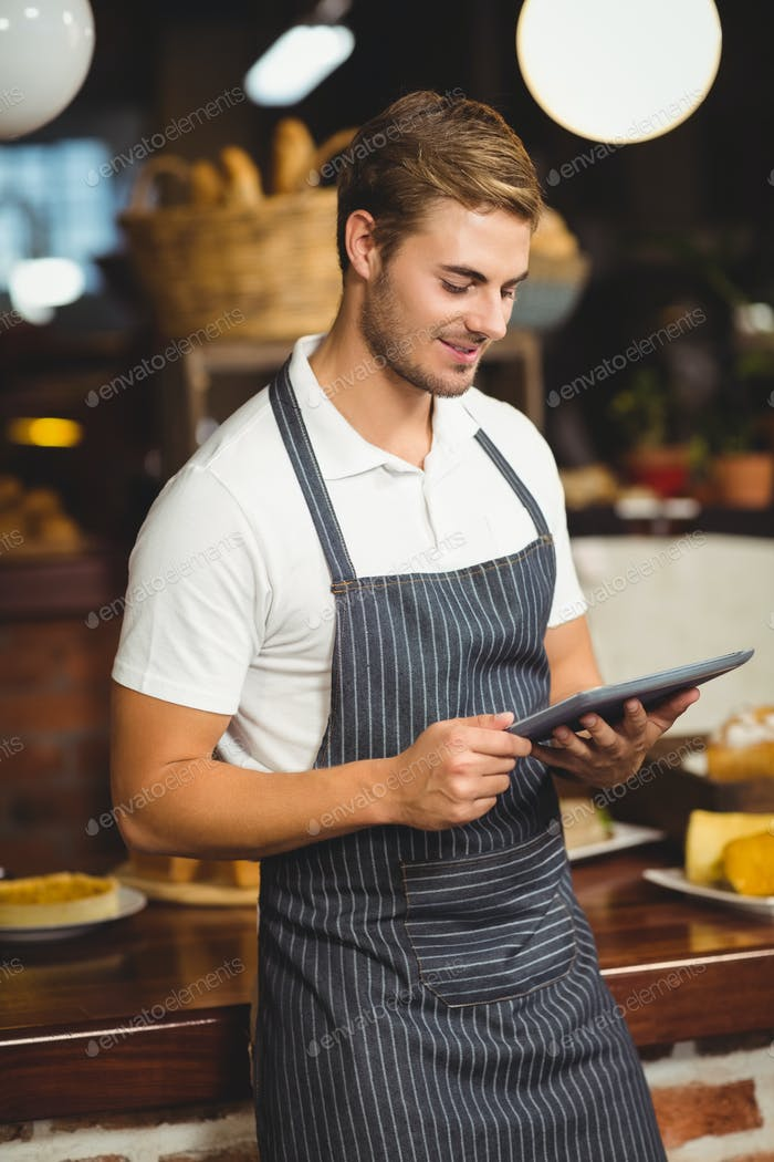 Handsome waiter using a tablet at the coffee shop