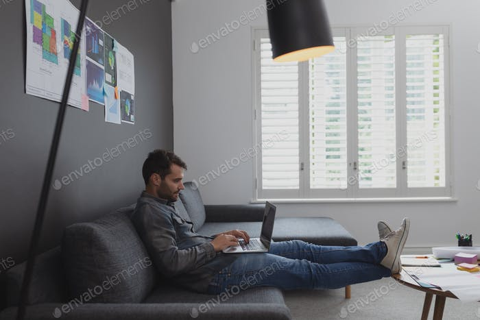 Side view of Caucasian male executive working on laptop on sofa in office