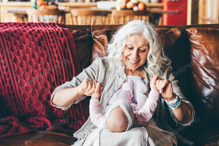 Aged lady with long loose grey hair plays with little granddaughter