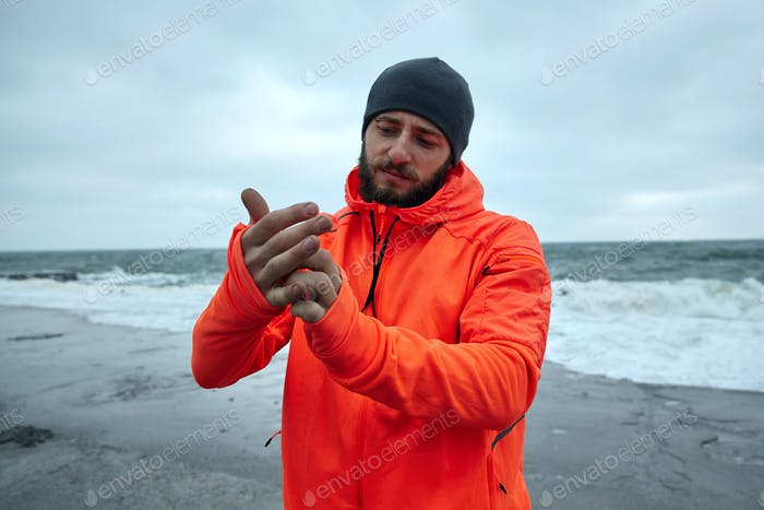 athletic brunette male with beard standing over seaside on grey stormy weather