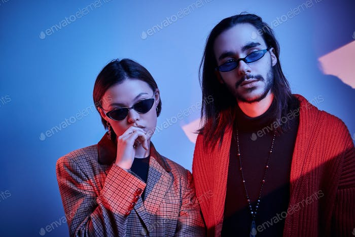 Couple of hipsters under red and blue lights