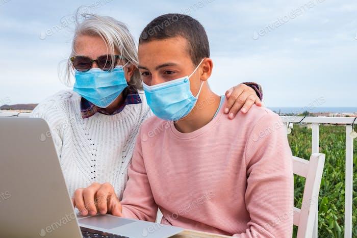 Großmutter und Enkel schauen auf Laptop auf der Terrasse. Tragen von OP-Maske Coronavirus