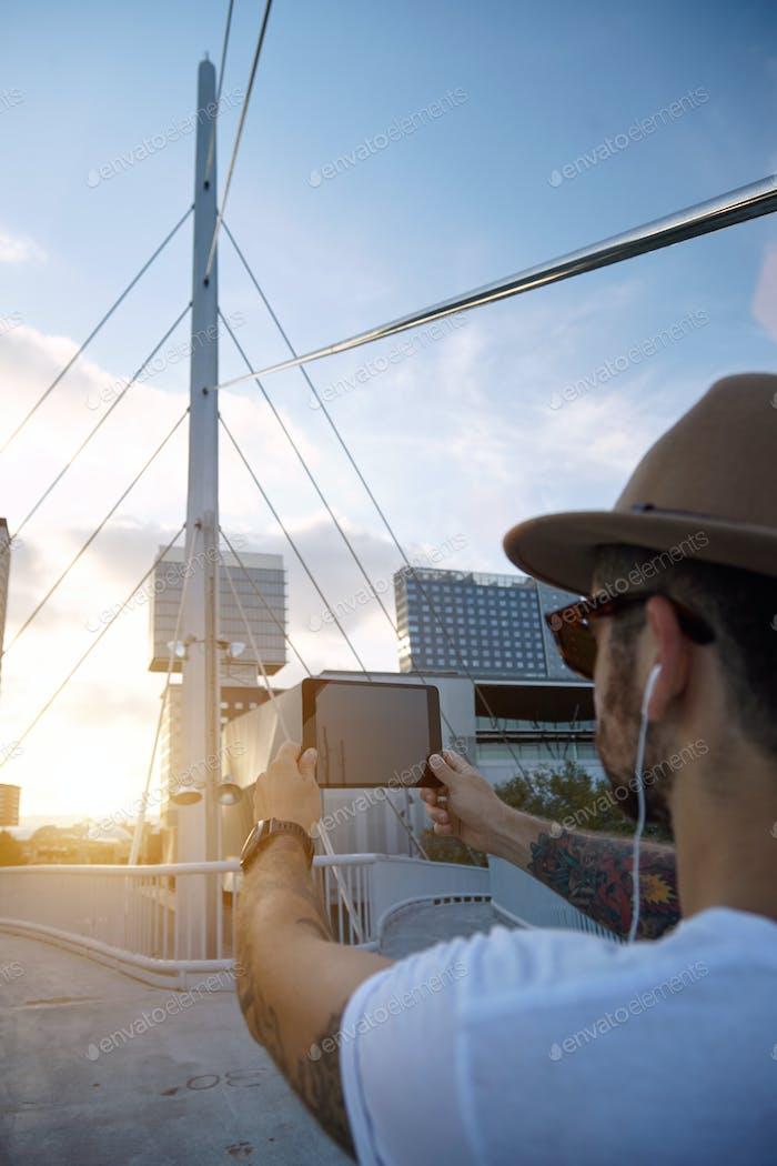 Turista toma una foto de la ciudad al atardecer
