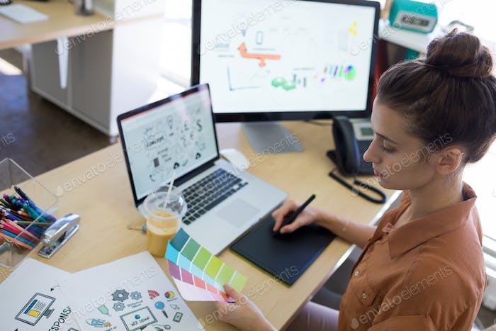 Female executive working over graphic tablet at her desk