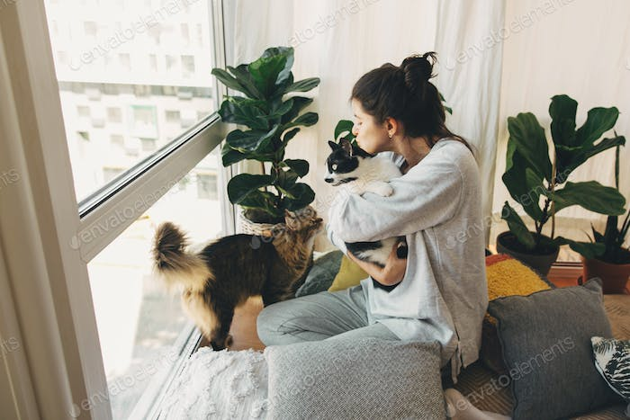 Hipster girl hugging and playing with two cats in modern room