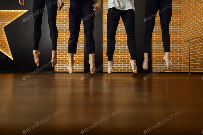 Contemporary dance studio, performers legs in jump