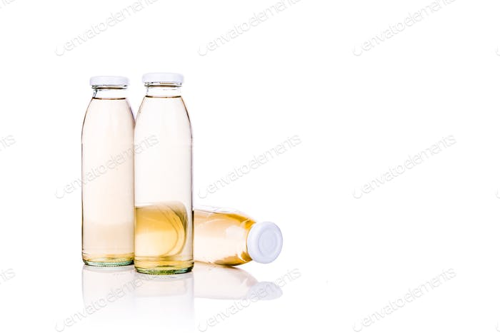 Translucent liquid in glass bottle on white background