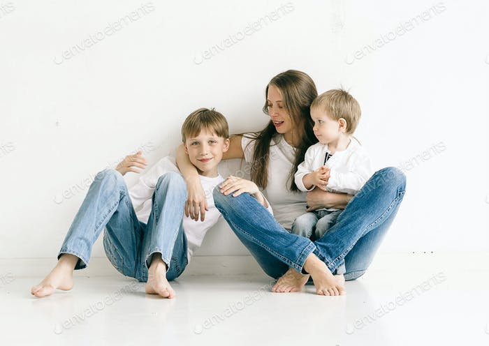 Family mother with children studio portrait full length in jeans on white background