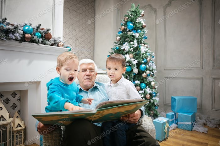 Senior man reading a book to grandsons at Christmas Eve