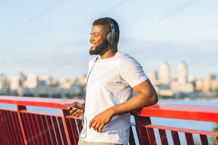 Joyful man having break while exercising open air