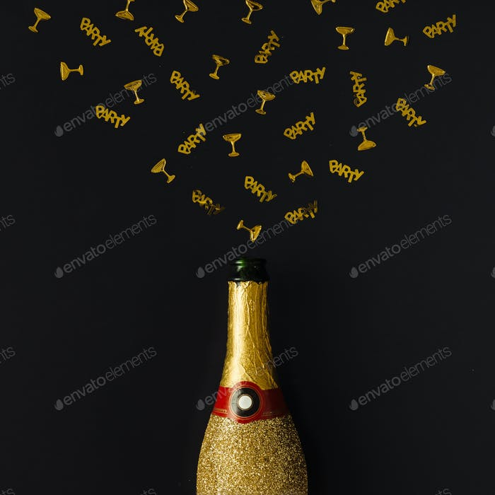 Golden champagne party bottle with confetti on dark background. Flat lay. Celebrate concept.