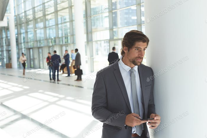 Businessman with mobile phone looking away in lobby office