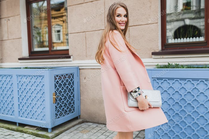 portrait of attractive stylish smiling woman walking city street in pink coat