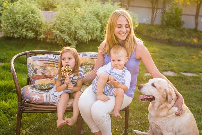 Mutter und ihre Kinder Entspannend im Garten mit Haustier Hund