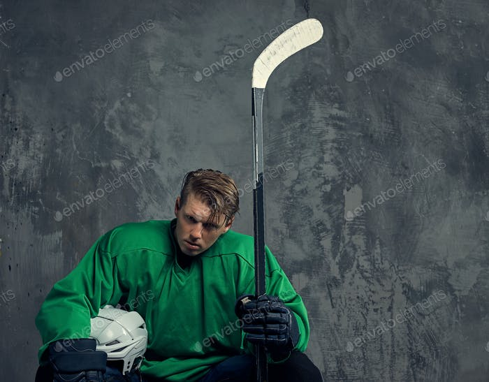 Hockey player wearing black protective uniform holds a hockey stick on a gray background.