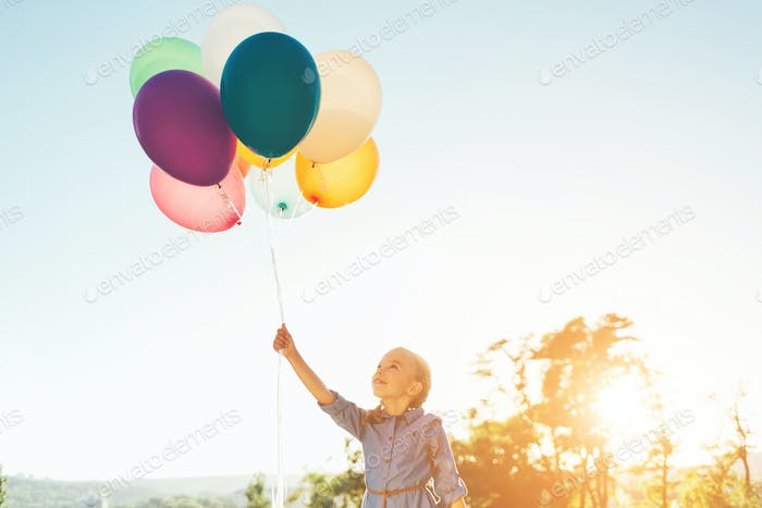 Girl holding balloons in one hand looking to them