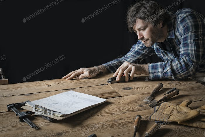 A man working in a reclaimed lumber yard workshop sanding knotted and uneven piece of wood.